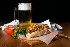 Hot dog americani con il vetro di birra con le bolle dolci Hot dog e patatine fritte sulla tavola su fondo scuro Immagine Stock Libera da Diritti