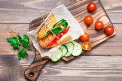Hot-dog appétissant fait à partir de la saucisse frite, des petits pains et des légumes frais, enveloppés en papier parcheminé su photos stock