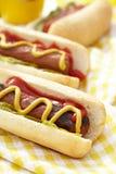 Hot dog arrostiti con senape, ketchup ed il condimento Fotografia Stock