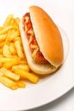 Hot-dog avec de la moutarde, le ketchup et les fritures Photo stock
