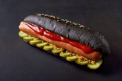 Hot dog in black bun Stock Image