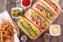 Hot dog on board. With sauce and french fries stock photography