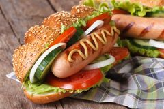 Hot dog in a bun with sesame seeds and grilled sausage Stock Photo
