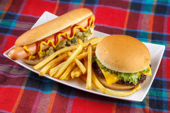 Hot dog, burger and fries. Hot dog , french fries and cheese burger on plate , fast food lunch on red fabric surface Stock Photos