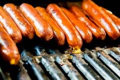 Hot dog che friggono sulla griglia all'aperto Fotografia Stock