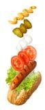 Hot dog con gli ingredienti di volo Immagine Stock Libera da Diritti