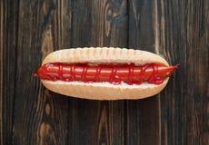 Hot dog con la salsiccia affumicata su fondo di legno scuro Foto con fotografia stock