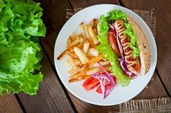 Hot dog con le patate fritte sul piatto bianco Fotografia Stock Libera da Diritti