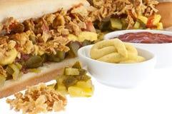 Hot dog con le salse in ciotole (percorsi di residuo della potatura meccanica) Fotografia Stock