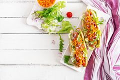 Hot dog with cucumber, carrot, tomato and lettuce on wooden background. Fast food menu. Top view stock image
