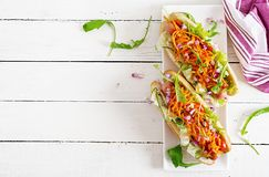 Hot dog with cucumber, carrot, tomato and lettuce on wooden background. Fast food menu. Top view stock images