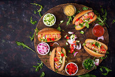 Hot dog with cucumber, tomato and red onion on wooden background. Top view. Flat lay royalty free stock image