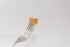 Hot-dog découpé en tranches sur la fourchette au-dessus du fond blanc Photographie stock libre de droits