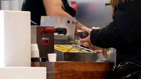 Hot dog d'acquisto della gente ad area della corte di alimento