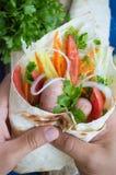 Hot dog a disposizione su peso - panino con la salsiccia in pita, carote coreane, pomodori, cipolle, prezzemolo e pepe Di legno Fotografie Stock
