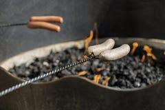 Hot dog e salsiccie di torrefazione sopra un fuoco di accampamento Fotografia Stock Libera da Diritti