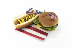 Hot dog ed hamburger su un tovagliolo e sugli stuzzicadenti della bandiera americana Fotografia Stock Libera da Diritti