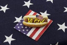 Hot dog ed hamburger su un tovagliolo e sugli stuzzicadenti della bandiera americana Fotografie Stock