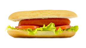 Hot dog with fresh leaf lettuce two slices of tomato and sliced cheese close up isolated on a white. Background stock photos