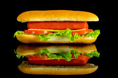 Hot dog with fresh leaf lettuce two slices of tomato and sliced cheese with reflection isolated on a black. Background stock image