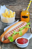 Hot dog with fresh lettuce and french fries on a wooden table Royalty Free Stock Images