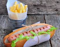 Hot dog with fresh lettuce and french fries on a wooden table Stock Image