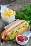 Hot dog with fresh lettuce and french fries on a wooden table Stock Photo
