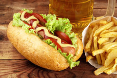 Hot dog with glass of beer with french fries on wooden board Stock Images