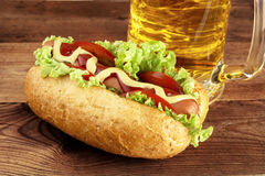 Hot dog with glass of beer on wooden board Royalty Free Stock Photo