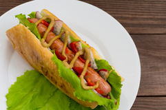 Hot dog with grilevskoy sausage, lettuce, radish and mustard, on a wooden background. Top view royalty free stock photos