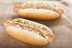 Hot dog grill with mustard, onion and pickles Stock Photo