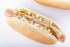 Hot dog grill with mustard, onion and pickles  on white Royalty Free Stock Images