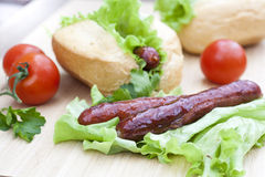 Hot dog. Grilled hot dogs with fresh salad lettuce on wooden table. Royalty Free Stock Image