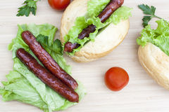 Hot dog. Grilled hot dogs with fresh salad lettuce on wooden table. Stock Photo