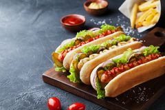 Hot dog with grilled sausage, ketchup, mustard and fries closeup. Traditional fast food. Hot dog with grilled sausage, ketchup, mustard and fries. Traditional stock photo