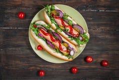 Hot dog Hot dog arrostiti con ketchup su una tavola di legno Immagine Stock Libera da Diritti