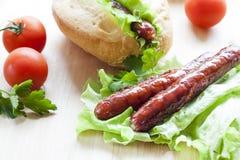 Hot dog Hot dog arrostiti con la lattuga fresca dell'insalata sulla tavola di legno Immagine Stock Libera da Diritti