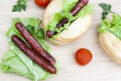 Hot dog Hot dog arrostiti con la lattuga fresca dell'insalata sulla tavola di legno Fotografia Stock