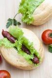 Hot dog Hot dog arrostiti con la lattuga fresca dell'insalata sulla tavola di legno Immagini Stock