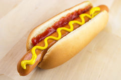 Hot dog. With ketchup and yellow mustard on wooden board Royalty Free Stock Images