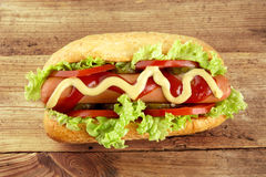 Hot dog with lettuce,tomatoes and cucumber on wooden board Royalty Free Stock Photos