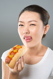Hot-dog lover. Vertical portrait of a pretty Asian girl licking her lips before tasting a hot dog stock photography
