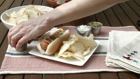 Hot Dog Lunch. Setting out hot dog with chips and condiments stock footage