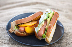 Hot dog. With mango slices, avocado, lettuce and mustard on a black plate Royalty Free Stock Images