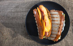 Hot dog. With mango slices, avocado, lettuce and mustard on a black plate Royalty Free Stock Photography