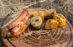 Hot dog. With mango slices, lettuce and mustard on a rustic wooden board with grilled potato and cron Royalty Free Stock Images