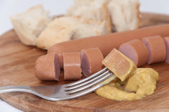 Hot dog with mustard on the fork Royalty Free Stock Photo