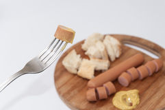 Hot dog with mustard on the fork Stock Photo