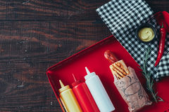 Hot dog with mustard, ketchup and mayonnaise on wooden background. Top view.  Stock Photos