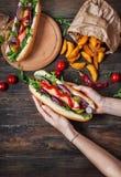 Hot dog nelle mani delle donne su una tavola di legno Immagini Stock Libere da Diritti